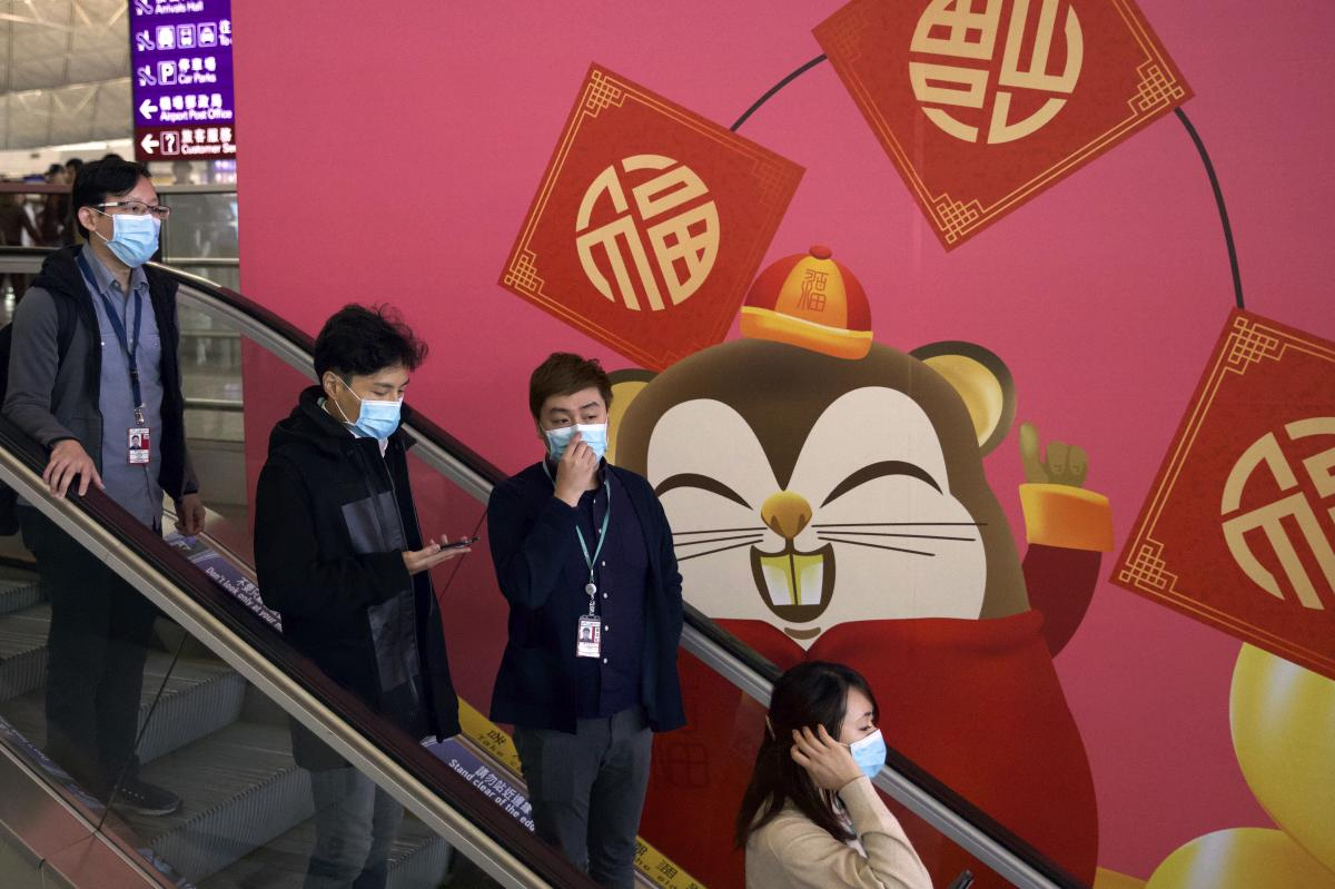 People wear face masks as they ride an escalator on Tuesday at the Hong Kong International Airport.