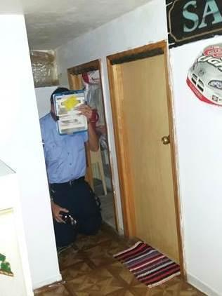 A New York City building inspector kneels to show the height of a small door and low ceiling inside Apartment 601, where nine illegal subunits were carved out of the Manhattan condo.