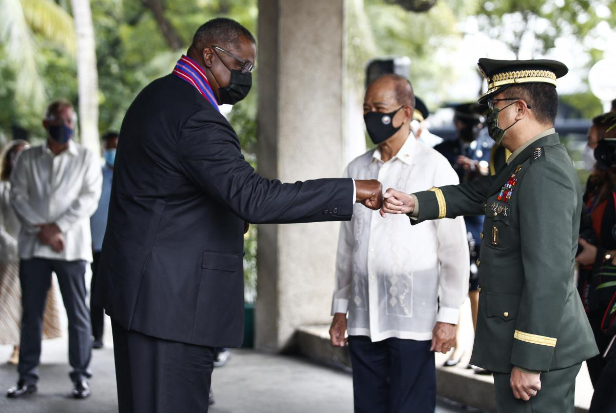 U.S. Defense Secretary Lloyd Austin (left) greets the chief of staff of the Armed Forces of the Philippines, Gen. Cirilito Sobejana (right), with a fist bump as Philippine Defense Secretary Delfin Lorenzana looks on at Camp Aguinaldo on July 30.