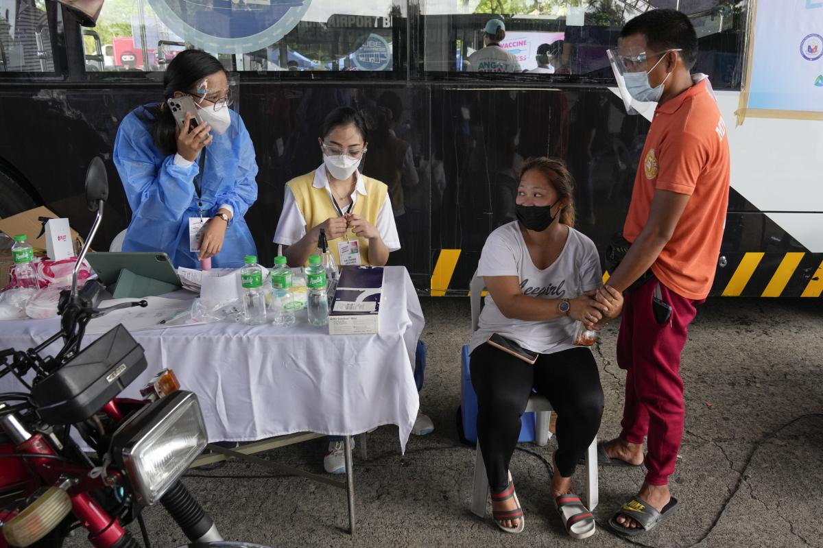 A woman holds the hands of her husband as they wait for a shot of the Sinovac COVID-19 vaccine at a drive-through vaccination center in Manila, Philippines, on June 22. Doubts have spread among Filipinos about the Chinese-made vaccine.