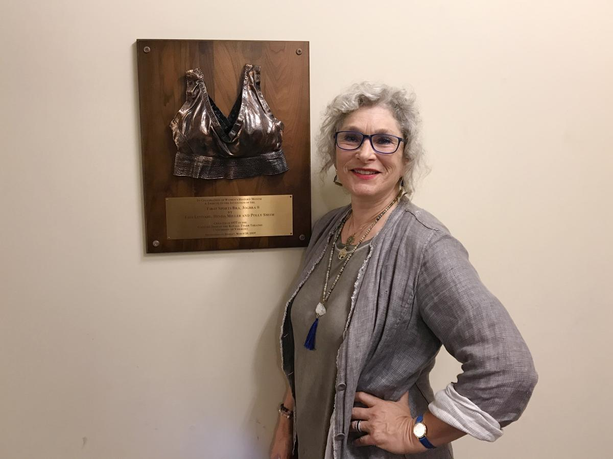 Hinda Miller stands by a bronze plaque at the University of Vermont that commemorates the Jogbra.