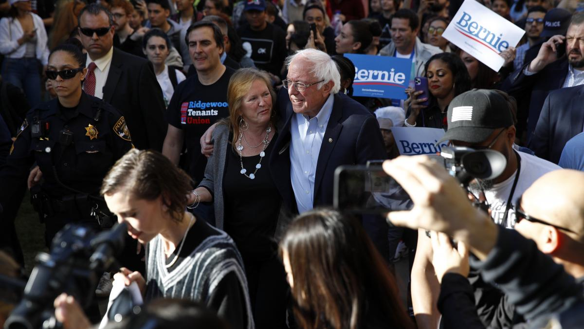 Democratic presidential candidate and Vermont Sen. Bernie Sanders and his wife, Jane O'Meara Sanders, lead supporters to an early voting location after a campaign event at the University of Nevada, in Las Vegas on Tuesday.