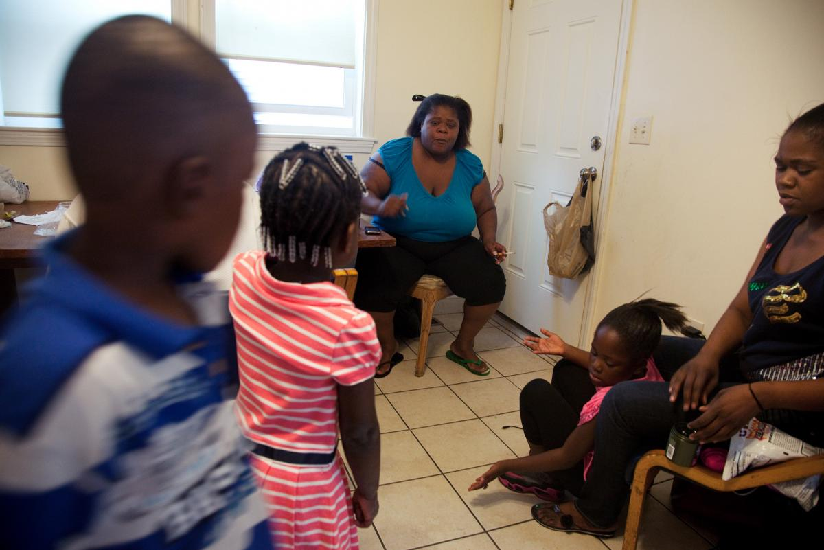 "Michelle Williams (center), at home in Dorchester, Mass., talks with grandchildren Ayniah Williams (pink dress) and Drequain Smith (far left). At right are her daughters Vanessa ""Nessa"" Williams (far right) and Margaret Williams. Both Michelle and Ayniah"
