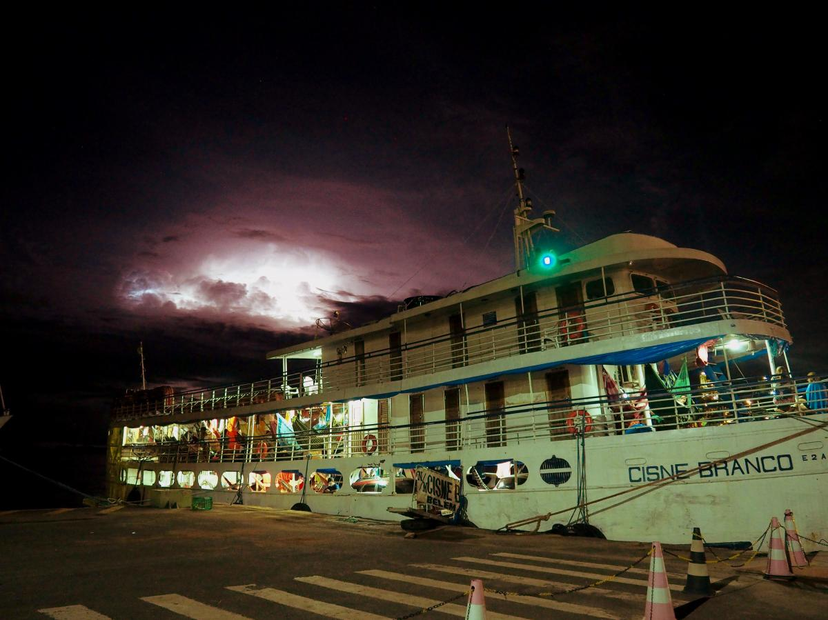 The White Swan docks for an overnight stop in the industrial city of Santarém in the northern Brazilian state of Pará. Heat lightning flashes through the night as passengers sleep in hammocks and crew fetch new cargo for the next leg of the journey.