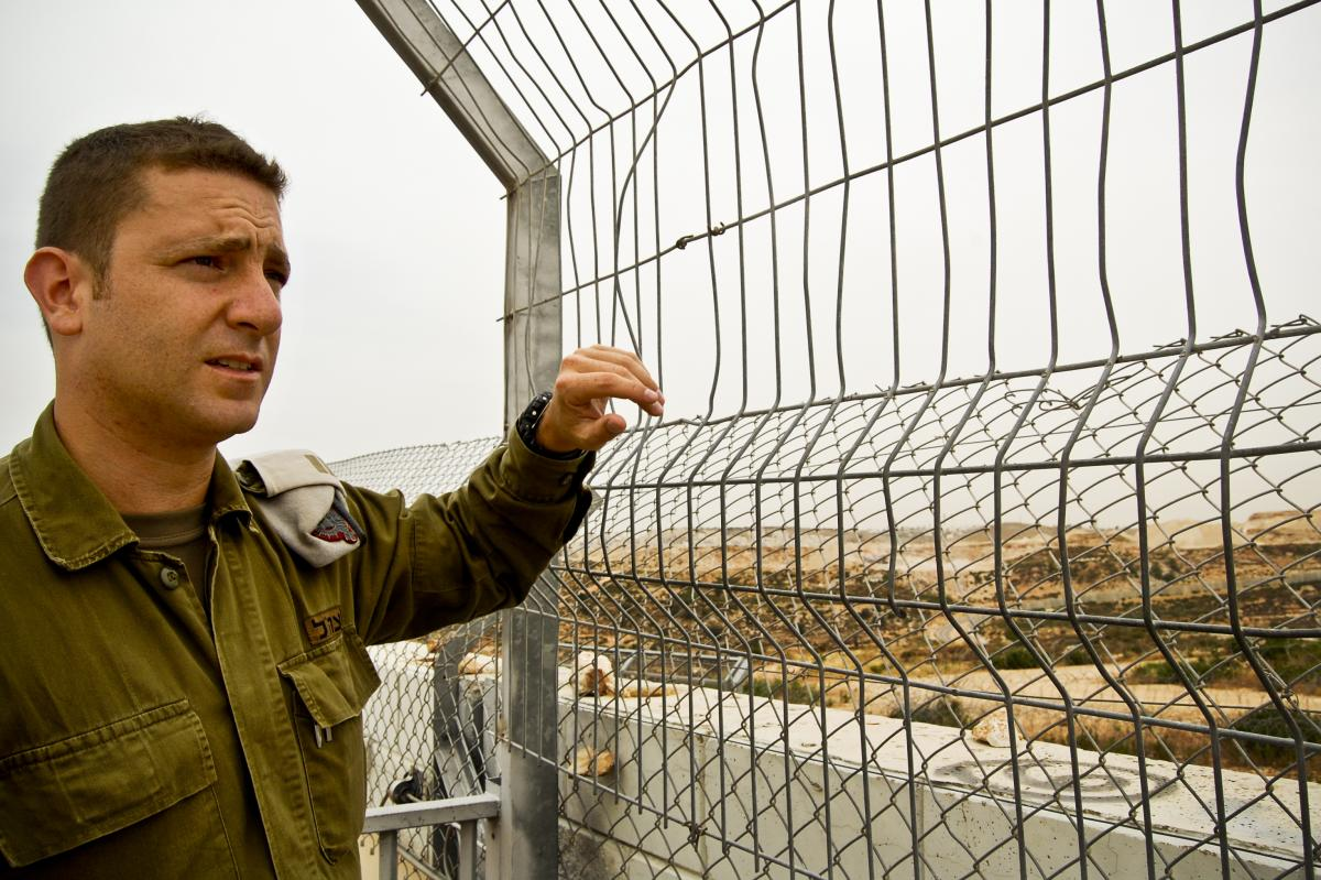 Israeli army Capt. Barak Raz stands on a concrete wall that is part of the barrier separating Israelis and Palestinians in the West Bank. Soldiers climb to this spot during Palestinian protests to disperse crowds with tear gas or a foul-smelling liquid ni