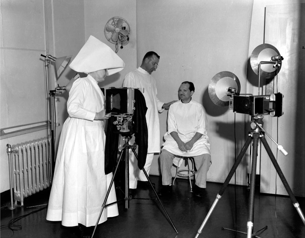 Sister Hilary Ross takes photos documenting a patient's treatment progress in the infirmary at the leprosarium in Carville, circa 1950. The photo was taken by Johnny Harmon, a patient with leprosy, for The Star, a magazine for the residents at Carville.