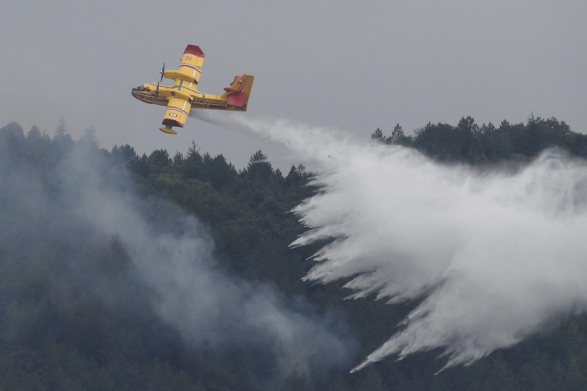 An airplane drops water to put out a forest fire near the village of Monze, southern France, on Aug. 15.