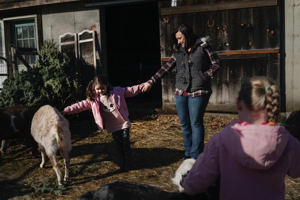 Mckinley and Addison play with their mom, Jennifer Ford, in the goat pen at their family home. Ford has recovered from her serious postpartum depression, after getting connected to therapy and other support through MCPAP for Moms.