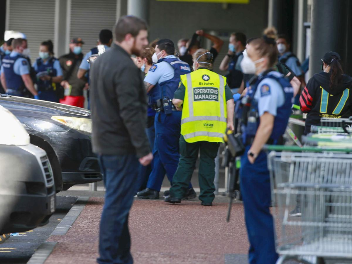 Police and ambulance staff attend a scene outside an Auckland supermarket, Friday, Sept. 3, 2021. New Zealand authorities said Friday they shot and killed a violent extremist after he entered a supermarket and stabbed and injured several shoppers.