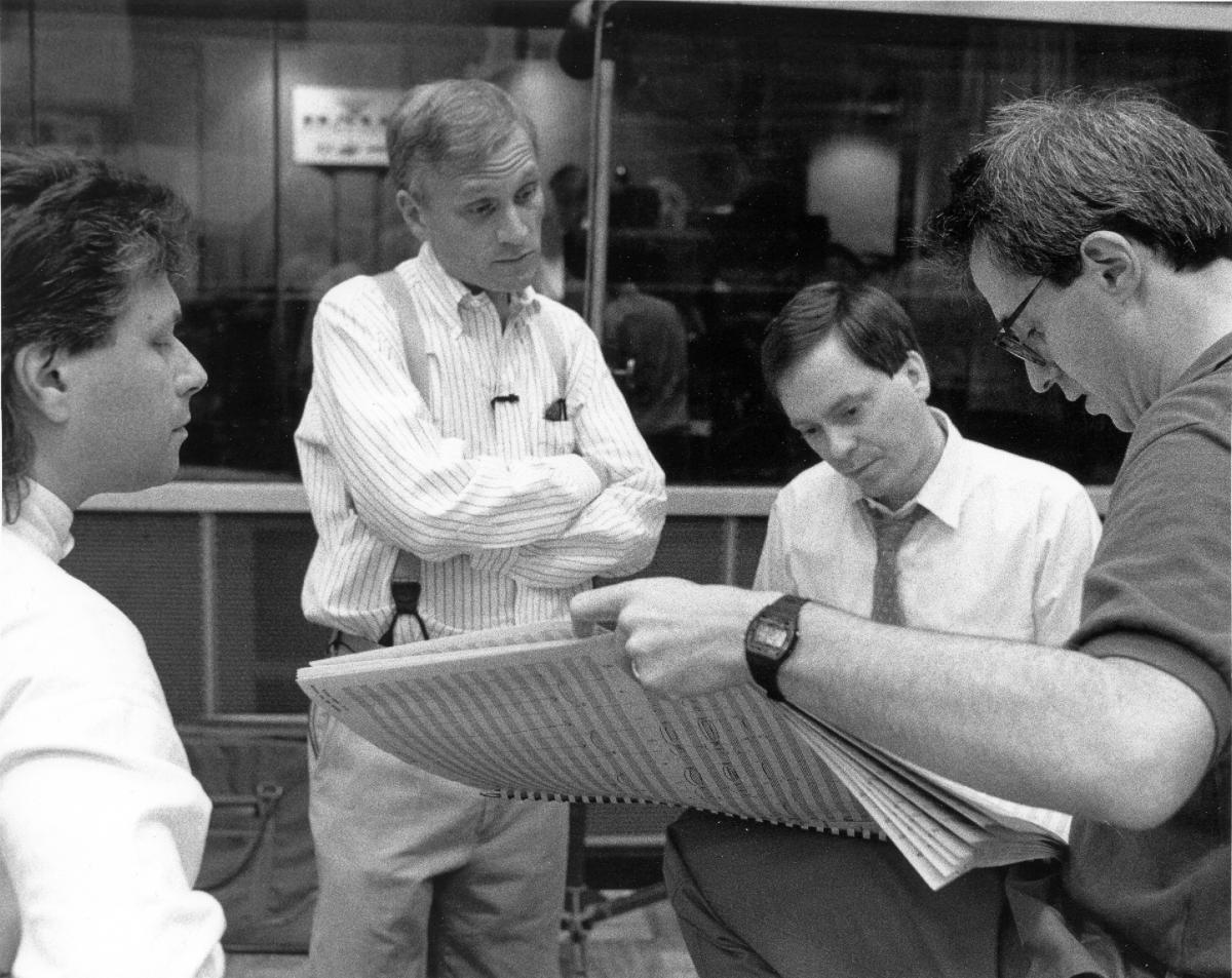 Composer Alan Menken (far left) and lyricist Howard Ashman (center-left) review a score with producer Don Hahn (far right).