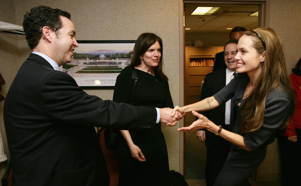 Charny, left, shakes hands with actor and U.N. Goodwill Ambassador Angelina Jolie at a Washington, D.C., event in 2007. At the time, he was on the board of the Cambodian Health Committee.