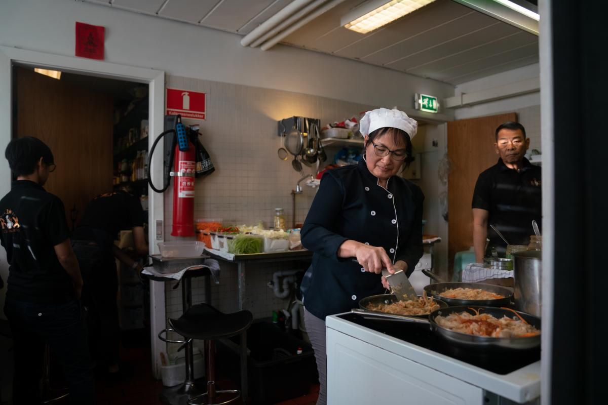 Siripen Paprajong, Suriya's wife, cooks in the kitchen of the restaurant.