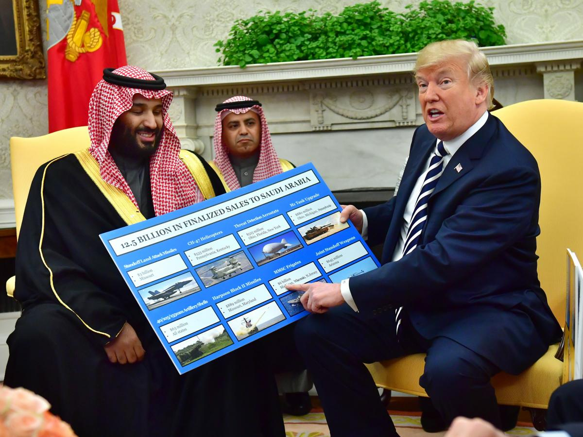 Saudi Crown Prince Mohammed bin Salman (left) meets with Trump, who holds a chart displaying military hardware sales, in the Oval Office of the White House in March 2018.