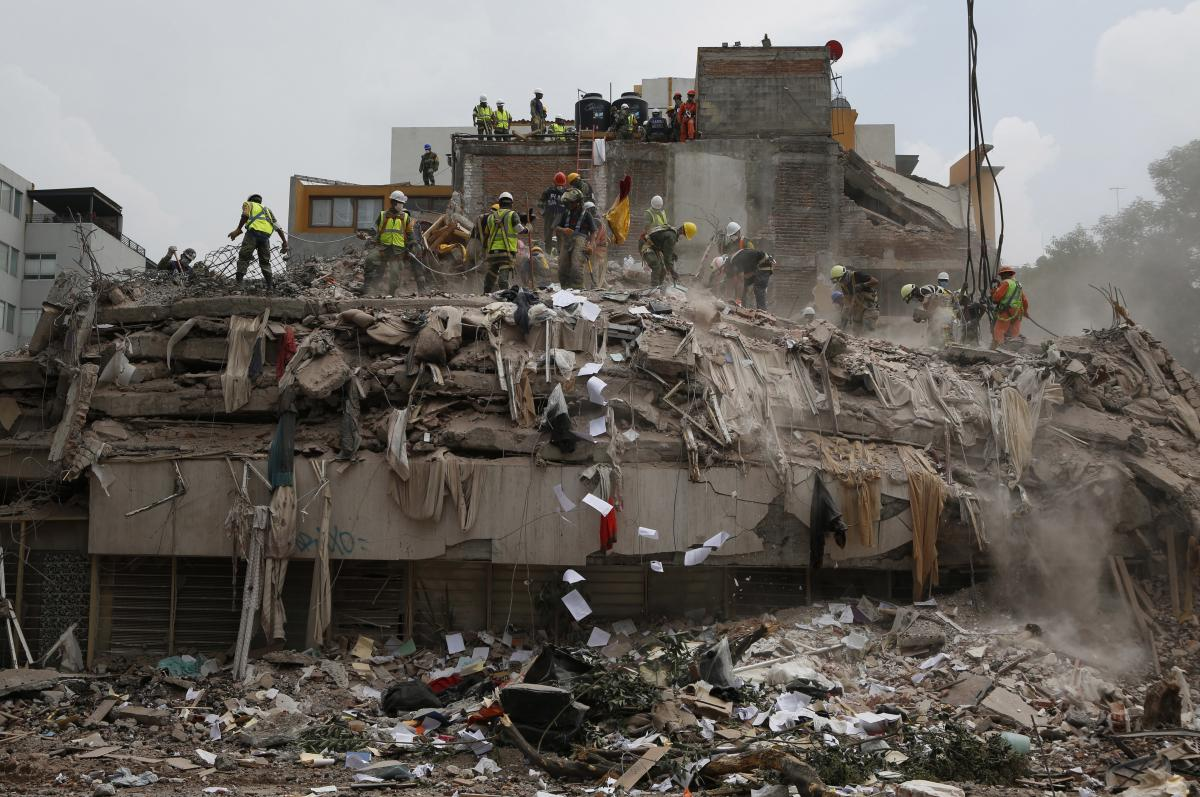 In Mexico City, workers shovel debris off the top of the rubble of a building that collapsed in 2017's 7.1 magnitude earthquake.