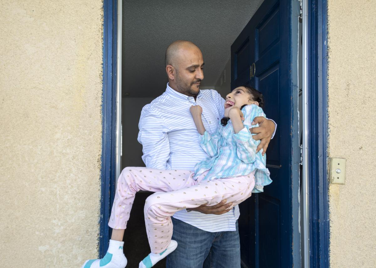 Nageeb Alomari holds his 10-year-old daughter, Shaema, in their front doorway just as he did outside the U.S. Embassy in Djibouti. Nageeb is from Yemen, but became an American citizen in 2010, and later applied for visas for his wife and daughters. Becaus