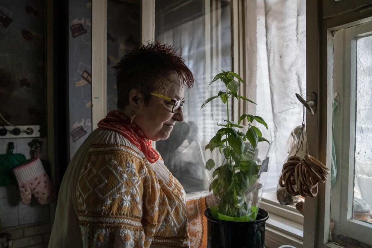 """Draghici stands in her kitchen with a plant. She says she's hopeful. """"Our wins are slim at this time, but they're there,"""" says Draghici."""