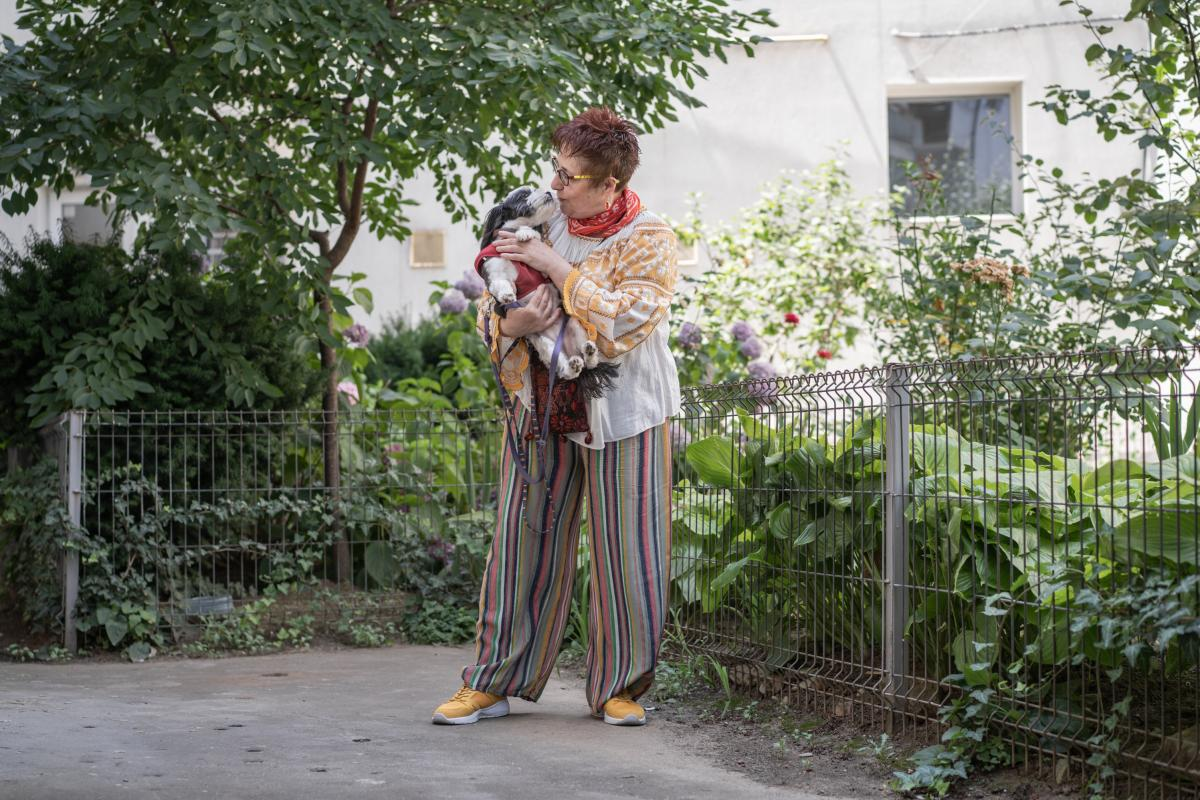 Daniela Draghici holding her dog, Mini, while on a walk in the backyard of her apartment building in Bucharest.