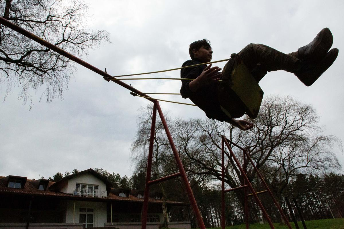 Mohammad Bilal, 17, from Afghanistan, plays on a swing at Bogovadja asylum center in central Serbia. He reached Serbia alone after smugglers in Iran put him in the trunk of a car alongside four other children with no water and amid scorching temperatures.