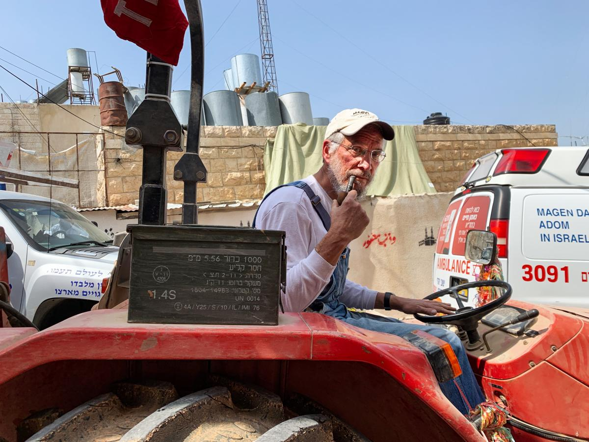 Chicago native and Hebron settler Yisrael Zeev is in costume as a pipe-smoking farmer and driving a float in the Purim parade. A red swath from the uniform of an international observer from the recently expelled Temporary International Presence in Hebron