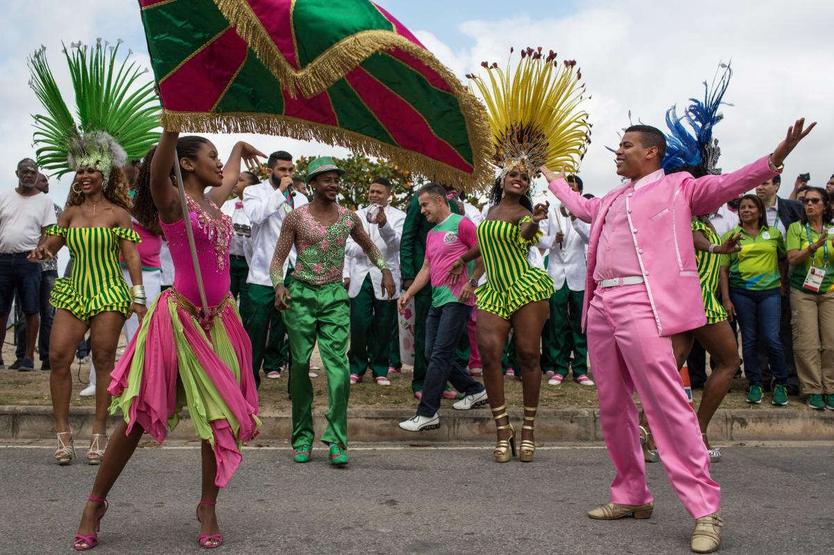 Dancers from the Mangueira samba school perform in the street Thursday while waiting for the arrival of the Olympic flame ahead of the games, which open Friday in Rio de Janeiro. The flame will be carried through the streets of Rio to Maracana Stadium for