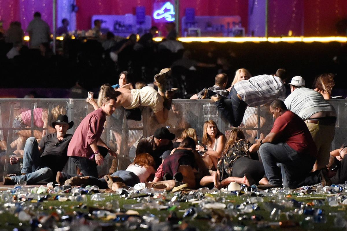 People scramble for shelter at the Route 91 Harvest country music festival in Las Vegas after gunfire was heard.