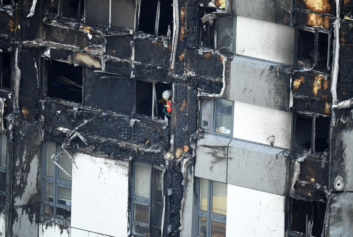 A firefighter is seen in a lower window of the burning 24-story residential Grenfell Tower block in West London on Wednesday.
