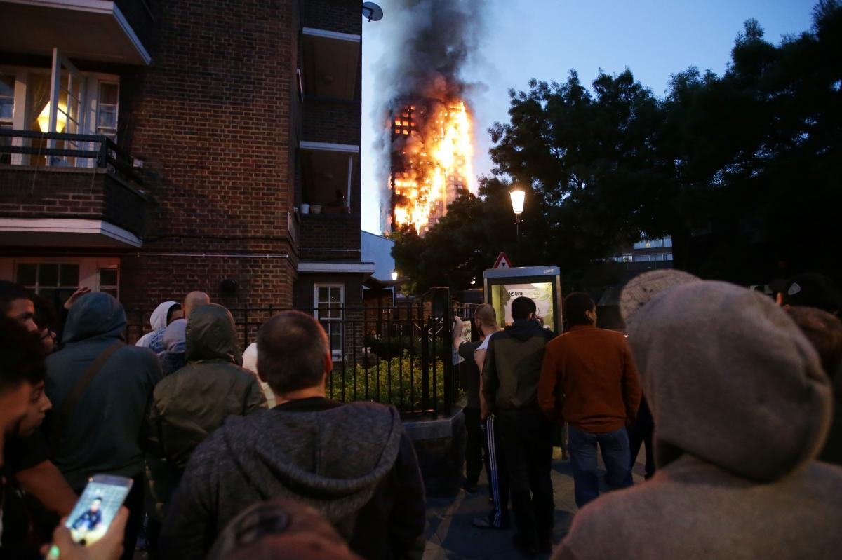Local residents watch as Grenfell Tower is engulfed by fire on Wednesday in west London. The massive fire trapped residents inside as 200 firefighters battled the blaze.