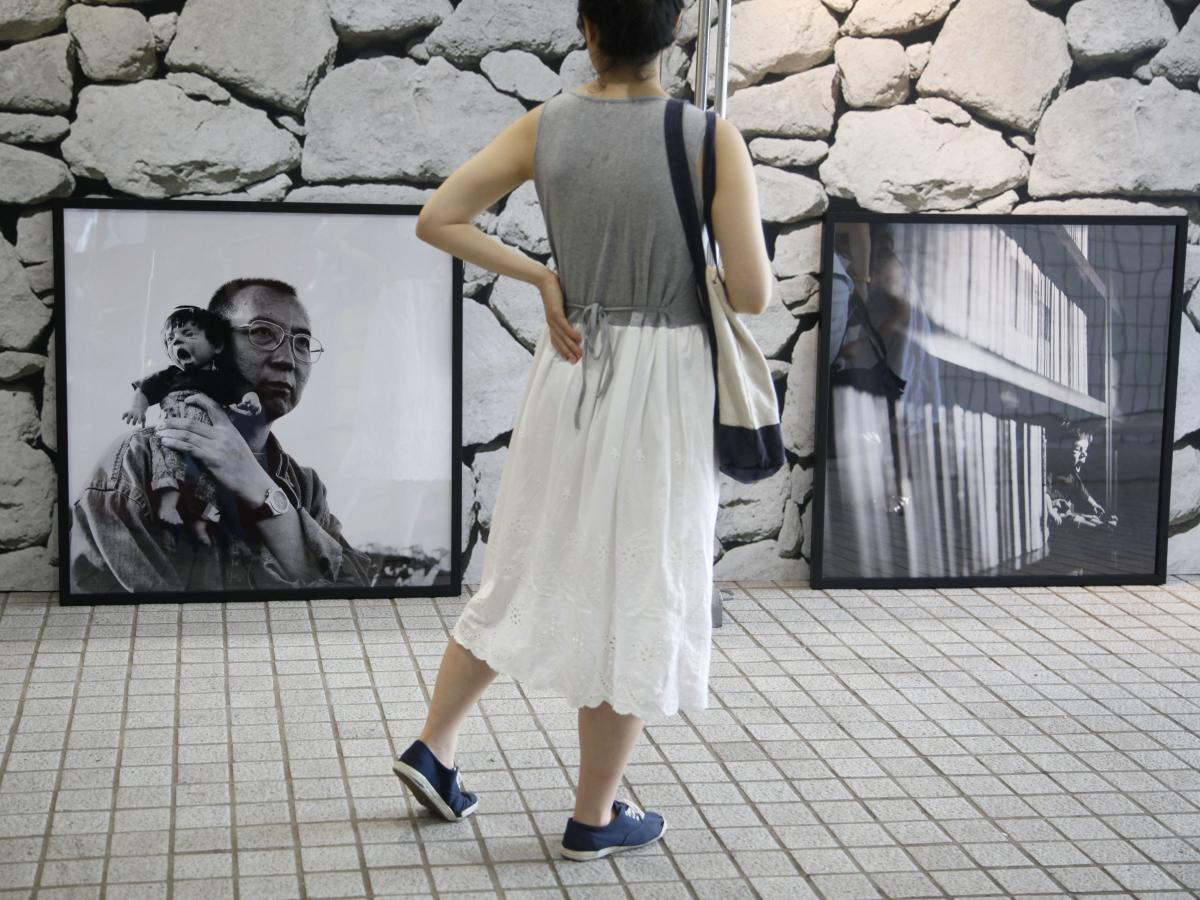 "A visitor looks at Liu Xia's photograph of her husband Liu Xiaobo holding a doll, during the 2012 ""Silent Strength of Liu Xia"" exhibition in Hong Kong. The photographer, painter and poet has been under house arrest for most of the time since her husband w"