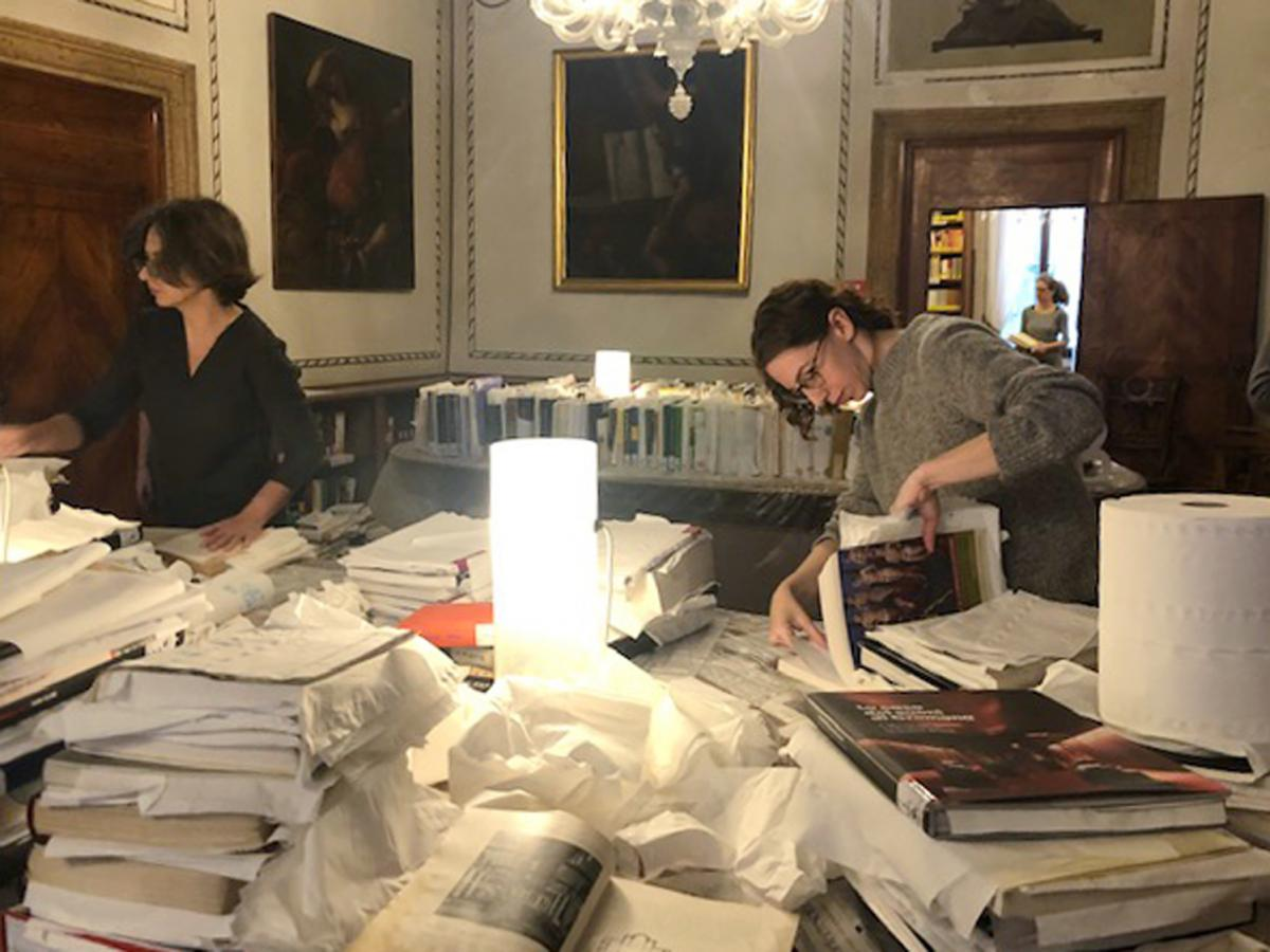 "At Venice's Querini Stampalia Foundation, volunteers including American student Anna Dumont (right) work to save books damaged in flooding. ""We're taking books that are wet with saltwater and we are, page by page, putting paper towels in between the pages"