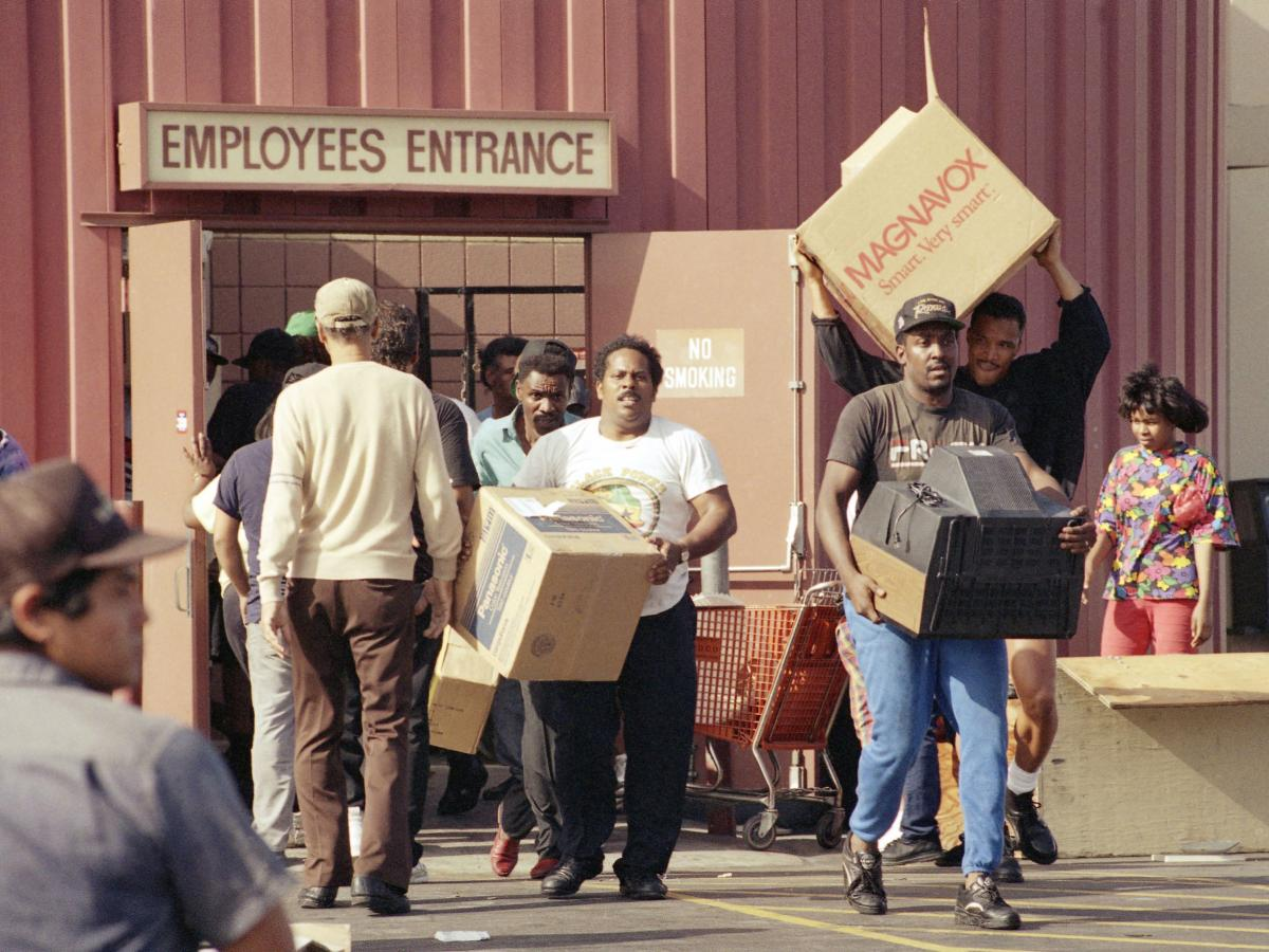 Looters carry televisions out of a Fedco Department Store at La Cienega Boulevard and Rodeo in Los Angeles on May 1, 1992, during the second day of rioting in the city.