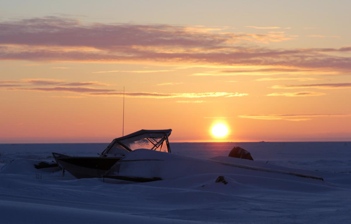 Boats buried in snow toward the edge of the lagoon at sunrise.