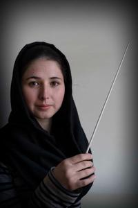 """Negin Khpolwak, who's 19, is one of the orchestra's two conductors. She has a bit of stage fright when she steps into the spotlight. Then, she says, """"I see the smile on the girls' faces when they play, and I don't think about anything else."""""""