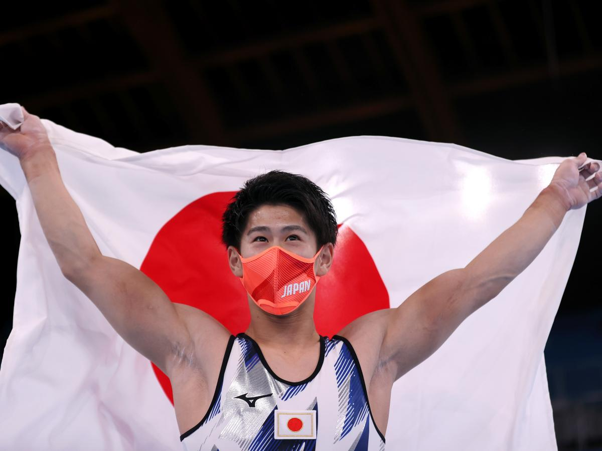 Daiki Hashimoto of Team Japan celebrates his victory with the Japan Flag during the Men's All-Around Final on day five of the Tokyo 2020 Olympic Games.