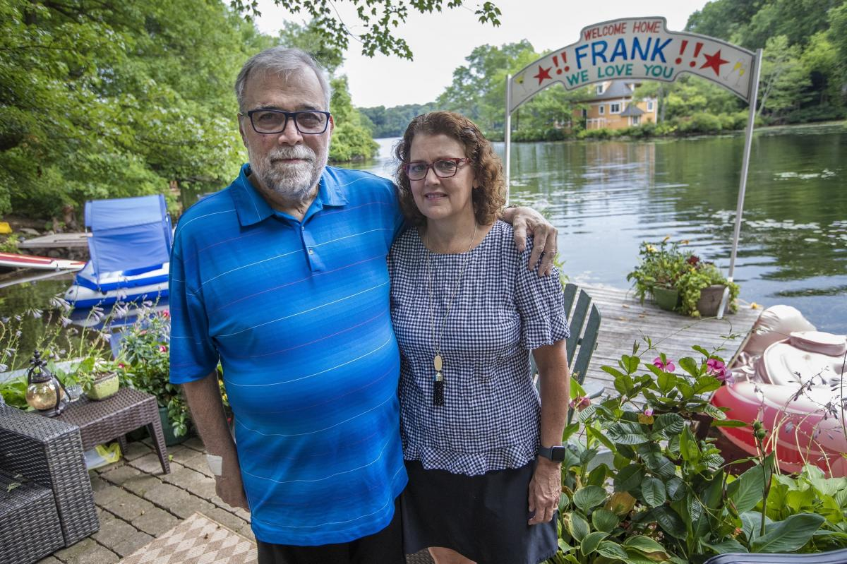 Frank and Leslie Cutitta at their home in Wayland, where a banner still hangs for his return from the hospital.