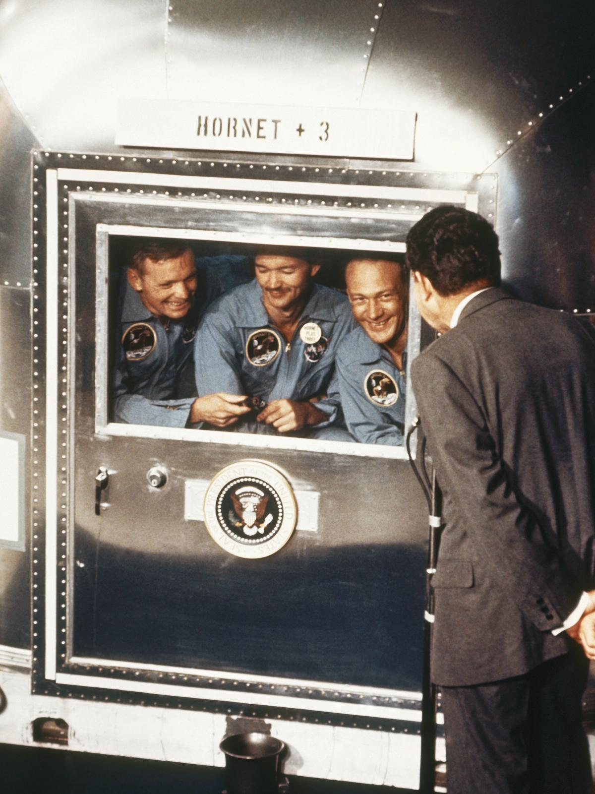 In 1969, President Richard Nixon greets the Apollo 11 astronauts in quarantine after their mission to the moon. The Apollo 11 crew members (from left) are Neil Armstrong, Collins and Buzz Aldrin.