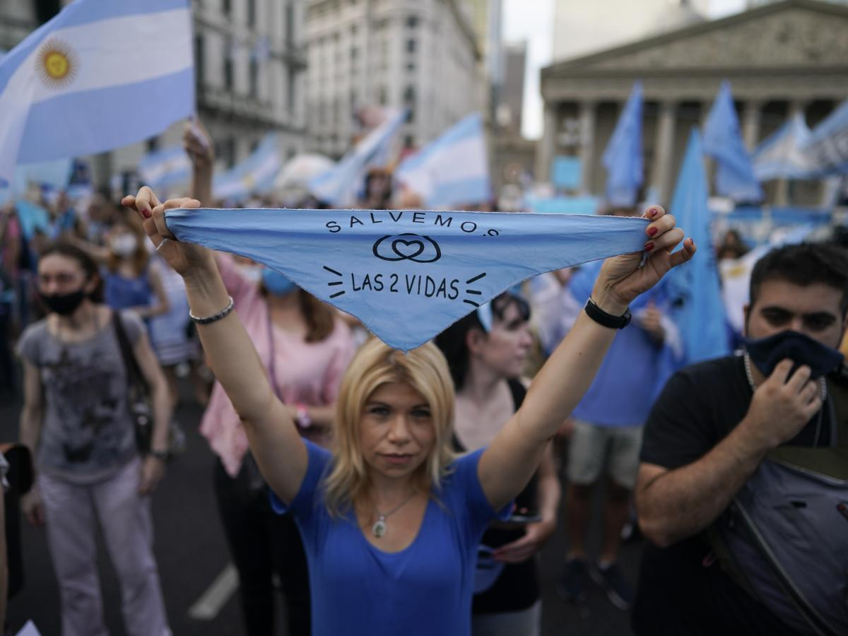 """An anti-abortion rights activist holds a handkerchief with text in Spanish that reads, """"save both lives,"""" as she protests against the decriminalization of abortion on Monday at Plaza de Mayo in Buenos Aires, Argentina."""