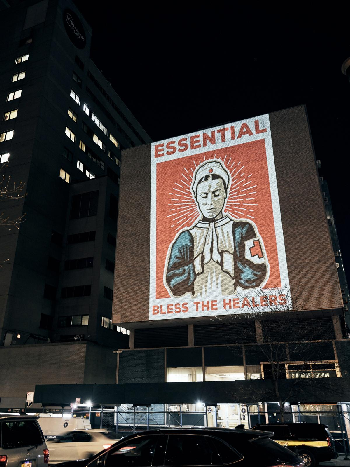"""""""Essential,"""" a poster design by Marvin Madariaga, is projected onto a hospital building in New York City. It was submitted to the arts group Amplifier's open call for pandemic art."""