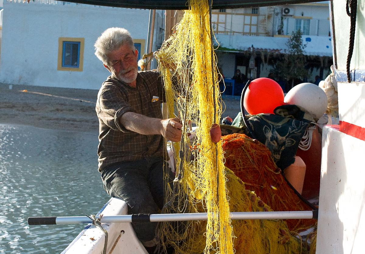 """Yiannis Tsakirios, 58, cleans a fishing net on the wooden caique he owns with his son, Parisi, docked at the village of Laki on the Aegean island of Leros. """"I work much longer hours now than I did as a young man,"""" he says."""