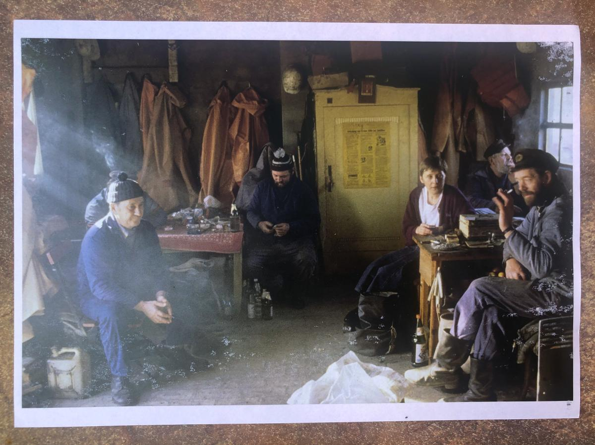 A photo of Hans-Joachim Bull's November 1990 picture with Angela Merkel, taken during Merkel's first campaign stop as a parliamentary candidate. Merkel chatted with Bull (far left, obscured behind another fisherman) and other fishermen in their hut. She a