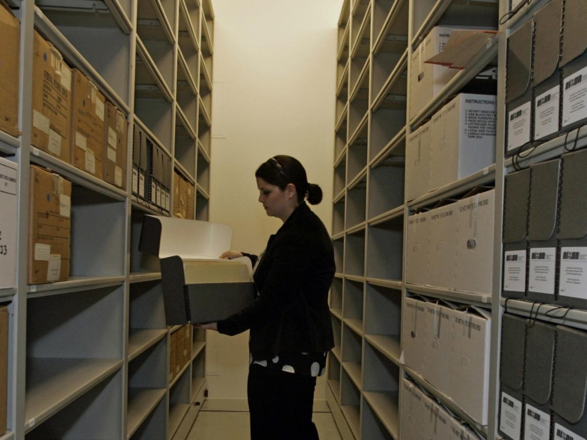 Nixon presidential library Archivist Meghan Lee looks at boxes containing the Committee for the Re-Election of the President collection's Jeb Stuart Magruder papers. Congress passed the Presidential Records Act out of concern that Richard Nixon would dest
