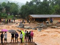 Floodwaters rage past a damaged building in Freetown, Sierra Leone, on Monday.