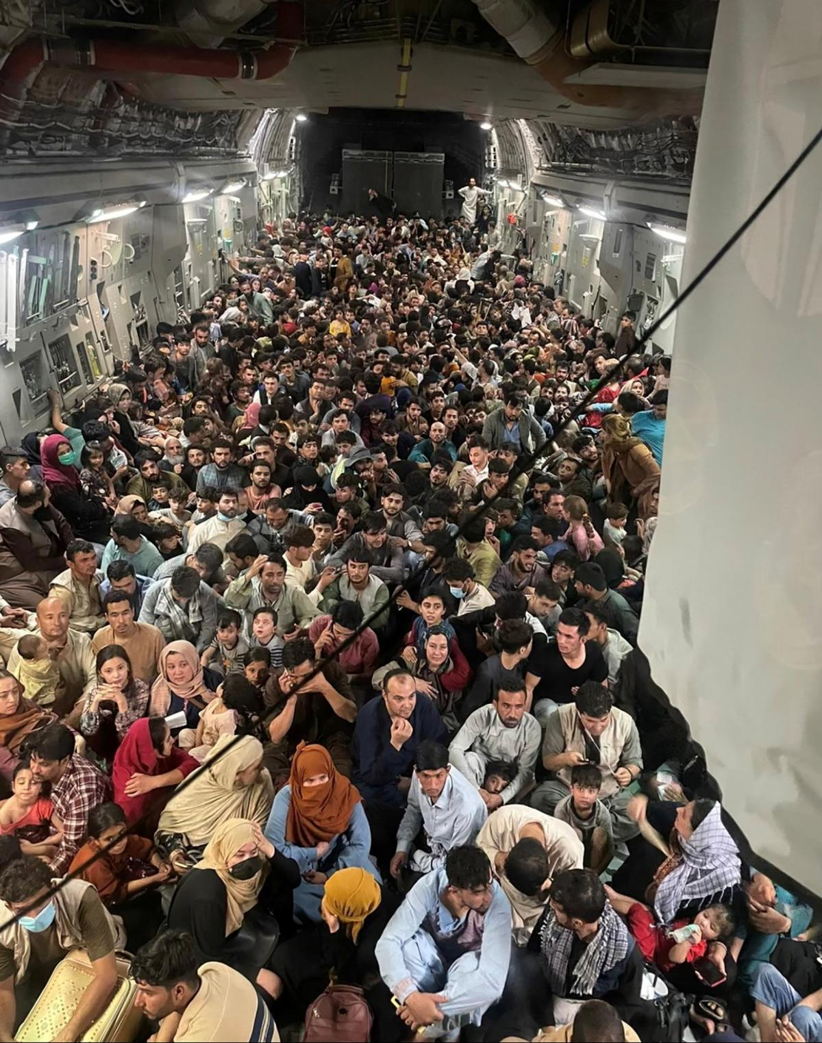 Evacuees crowd the interior of a U.S. Air Force C-17 Globemaster III transport aircraft, carrying some 640 Afghans to Qatar from Kabul on Sunday.