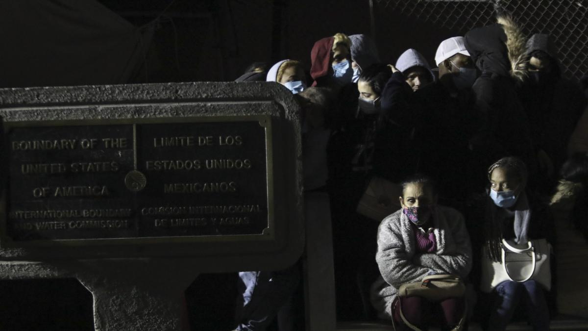 Migrants, mainly from Cuba, occupy the Mexican side of the Paso del Norte border bridge, where a plaque marks the border line, as they protest to be allowed into the U.S. to apply for asylum in Ciudad Juarez, Mexico, just before midnight on Dec. 29, 2020.