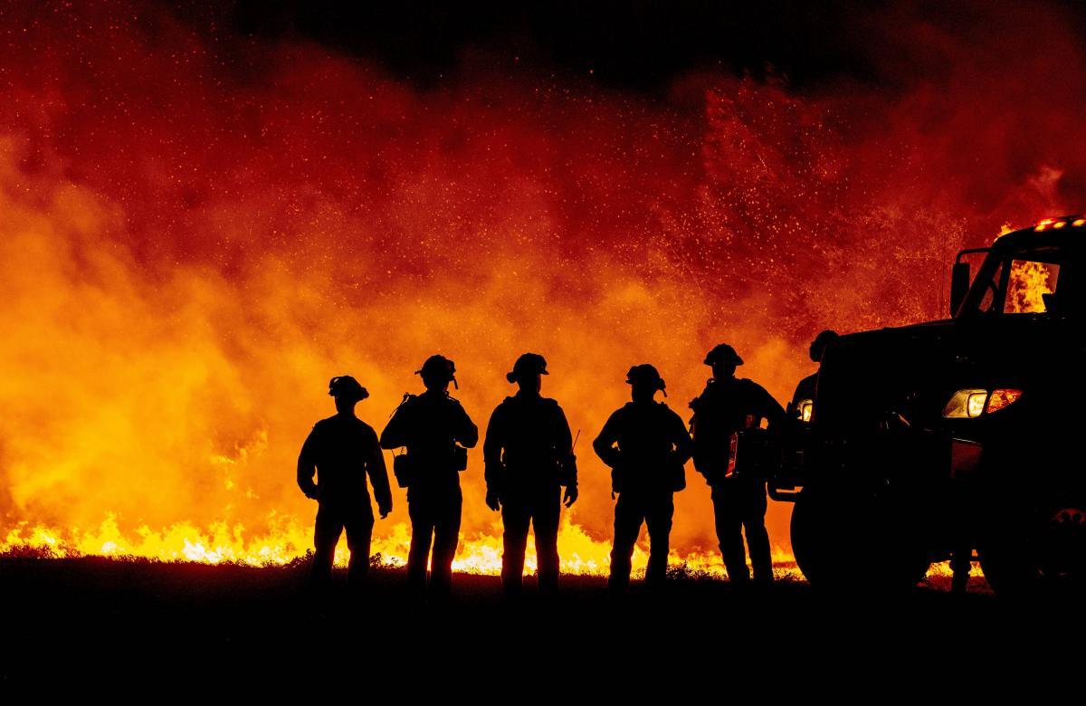 Butte County firefighters watch as flames quickly spread across a road at the Bear Fire in Oroville, Calif., on Wednesday. The local sheriff says three people died as a result of fires in the area.