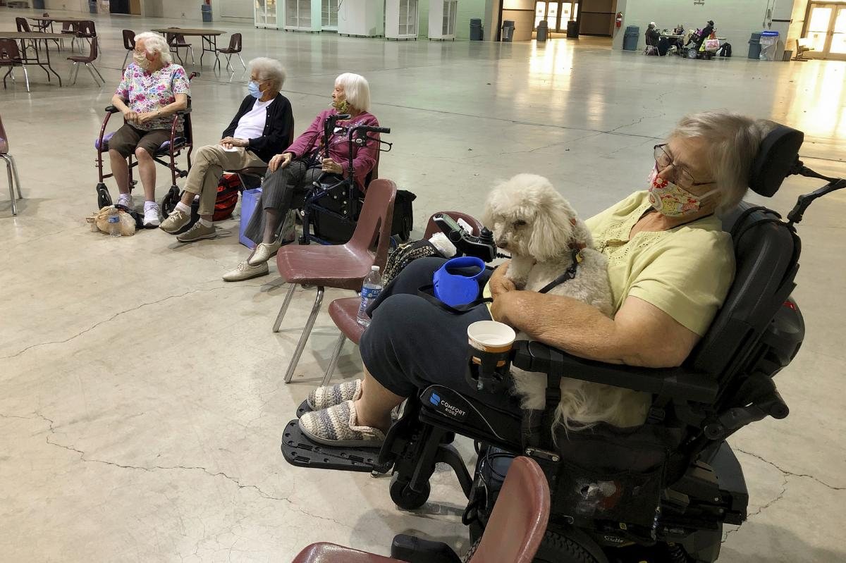 Patricia Fouts sits with her dog, Murphy, and other evacuated residents of a senior living home in an evacuation center at the Oregon State Fairgrounds in Salem, Ore., on Tuesday. Marian Estates senior living home in Sublimity, Ore., was evacuated early T