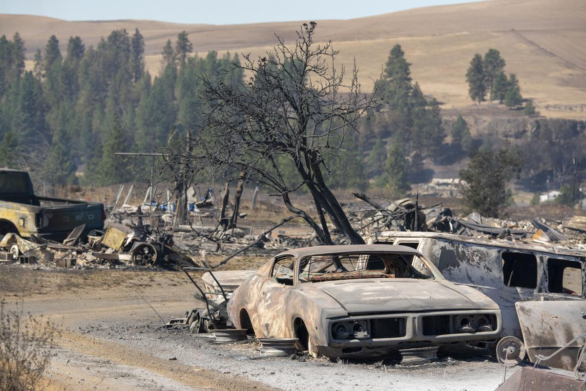 Vehicles were destroyed by a wildfire in Malden, Wash., on Tuesday. Large parts of the West Coast are under warnings for elevated fire weather threats Thursday, but there may be relief if fire-driving winds decrease as expected.