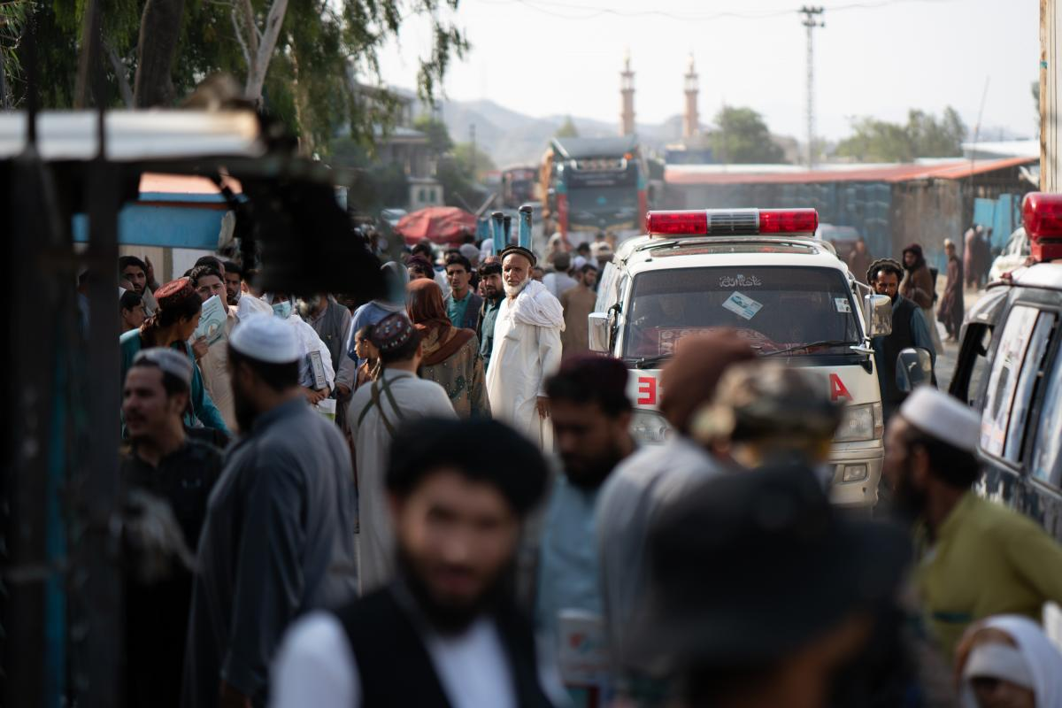 Taliban members and people waiting in Afghanistan can be seen from the Pakistani side of the border crossing at Torkham.