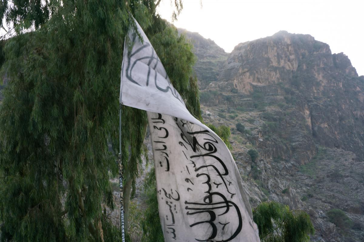 The Taliban flag hangs on the Afghanistan-Pakistan border, backdropped by the mountains of Pakistan's Khyber Pakhtunkhwa province.