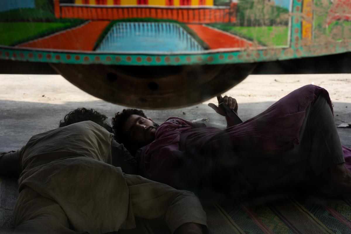 With border traffic at a standstill, men rest under a truck while waiting to get into Afghanistan.