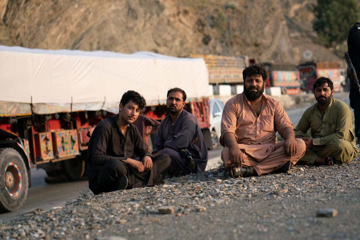 Razziq Mehmon (second from right) waits in Pakistan near the border to drive a truck loaded with cement bound for Jalalabad, Afghanistan.